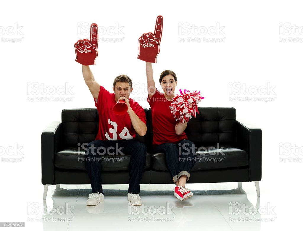 Football fans sitting on couch and cheering stock photo