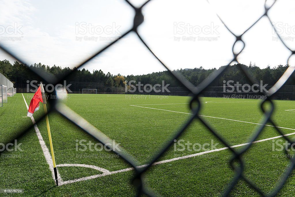 football field behind the chainlink fence stock photo