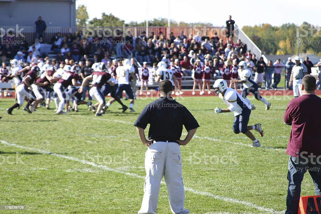 Football game with coach watching on side line stock photo