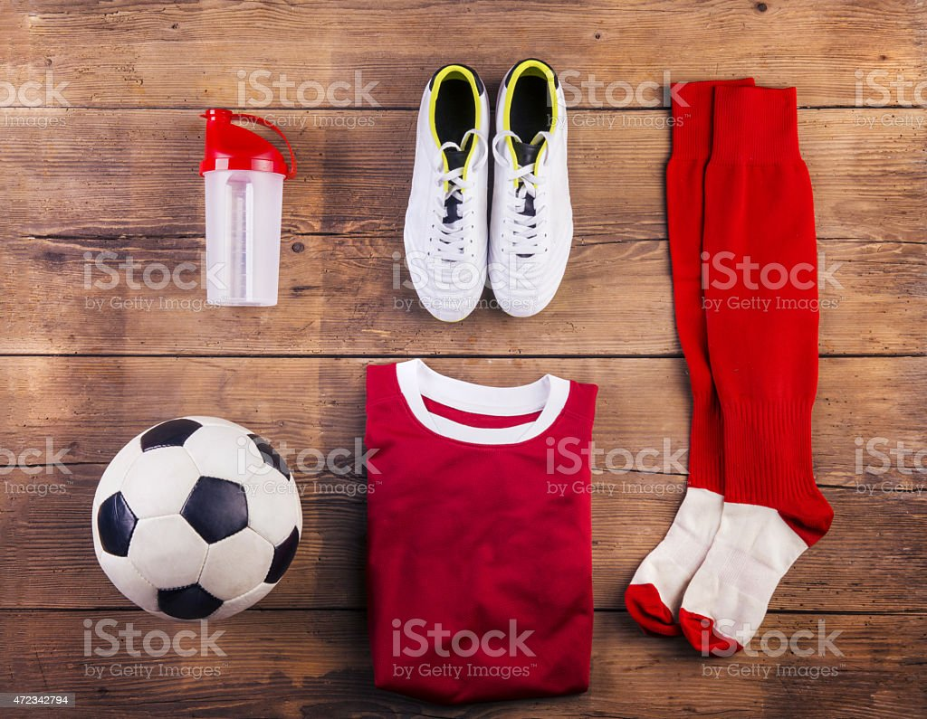 Football gear lying organized on a wooden floor stock photo