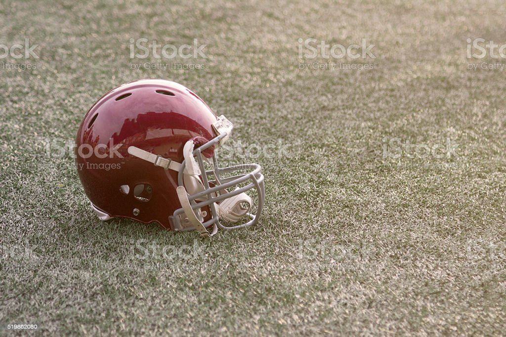 Football helmet lying on green grass field stock photo