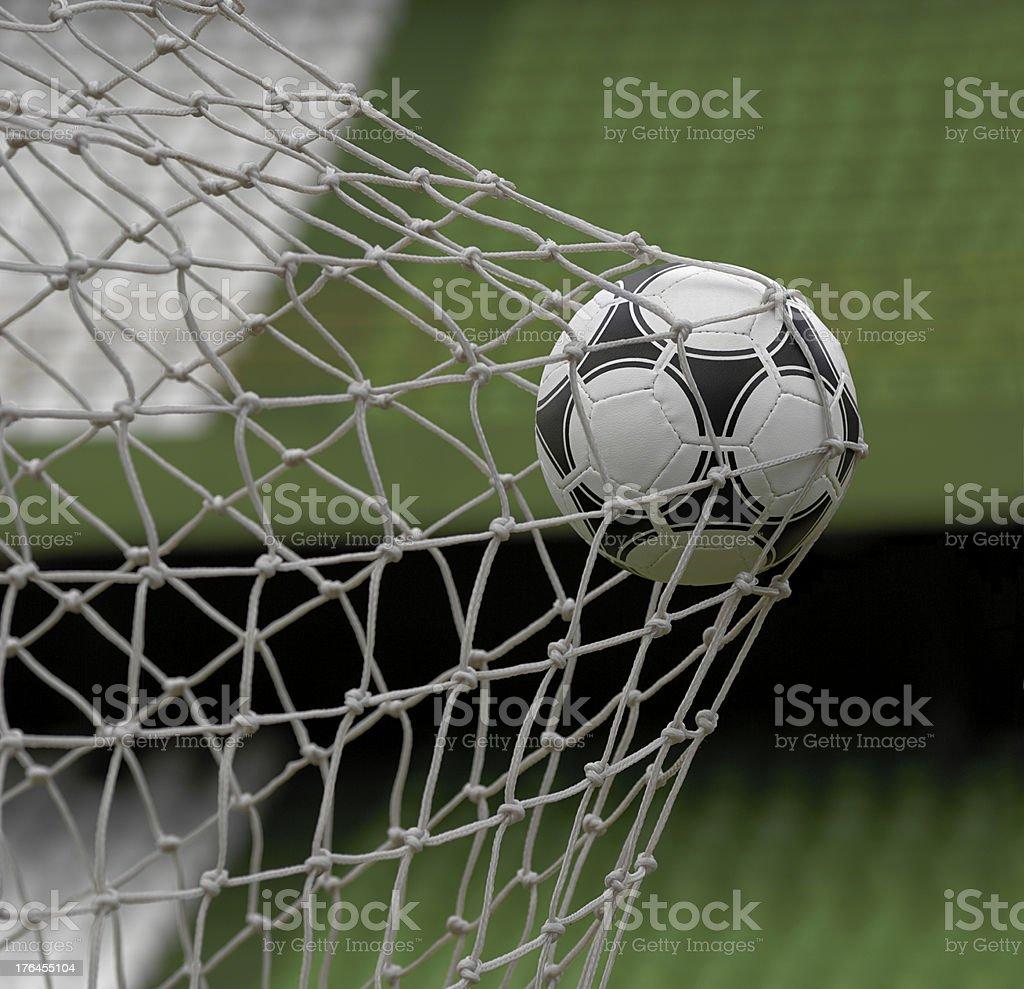 Football in back of goal net against stadium background stock photo