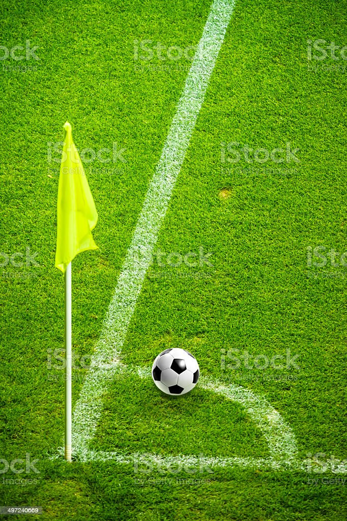 Football in corner with yellow flag on soccer field stock photo