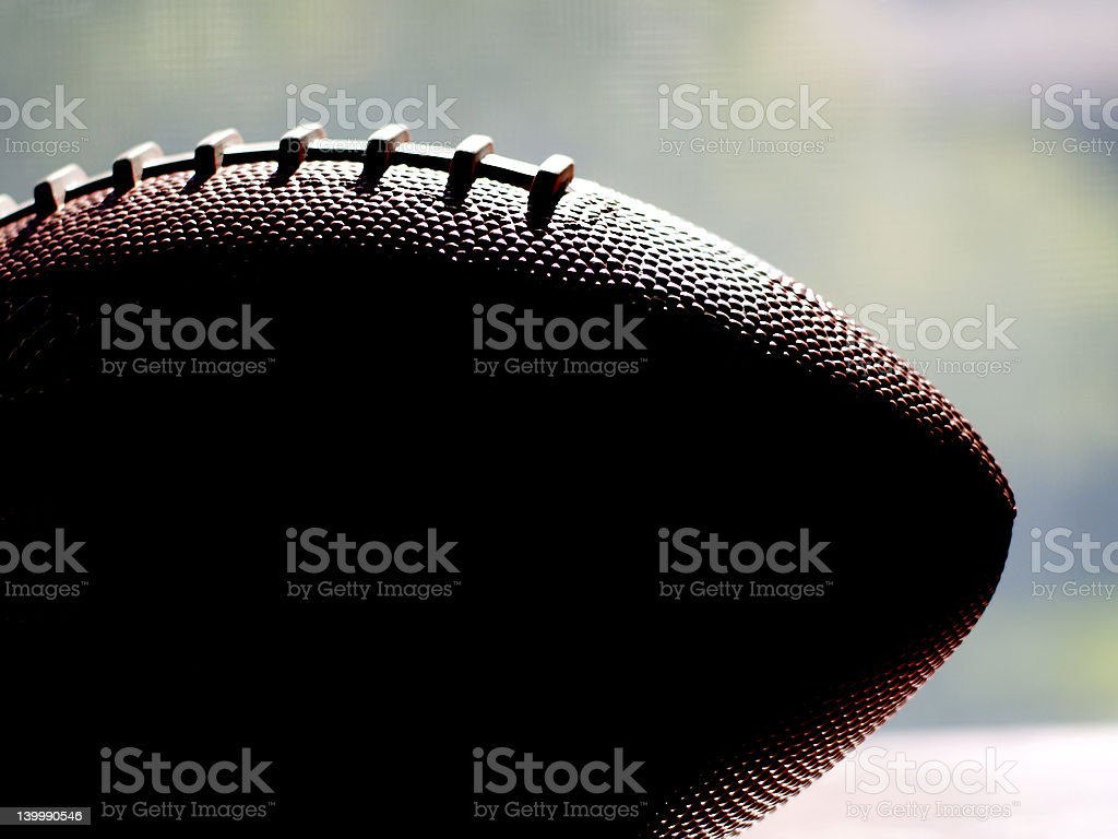 Football in silhouette against window stock photo