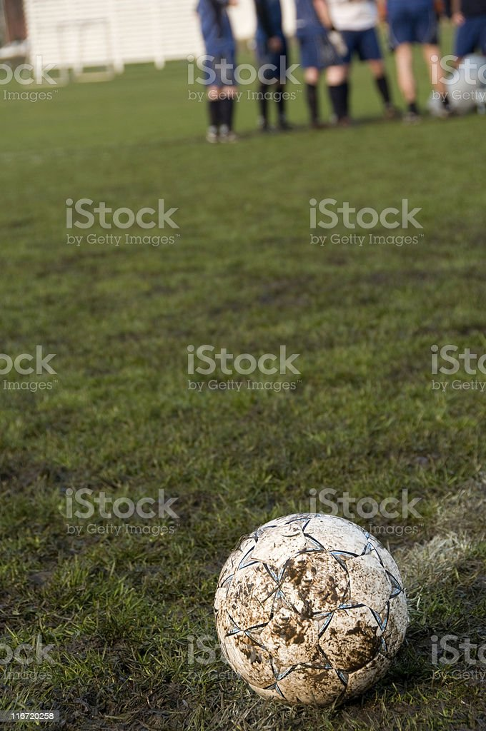 Football on a muddy football field royalty-free stock photo