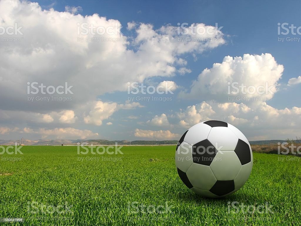 Football on green grass field game stock photo