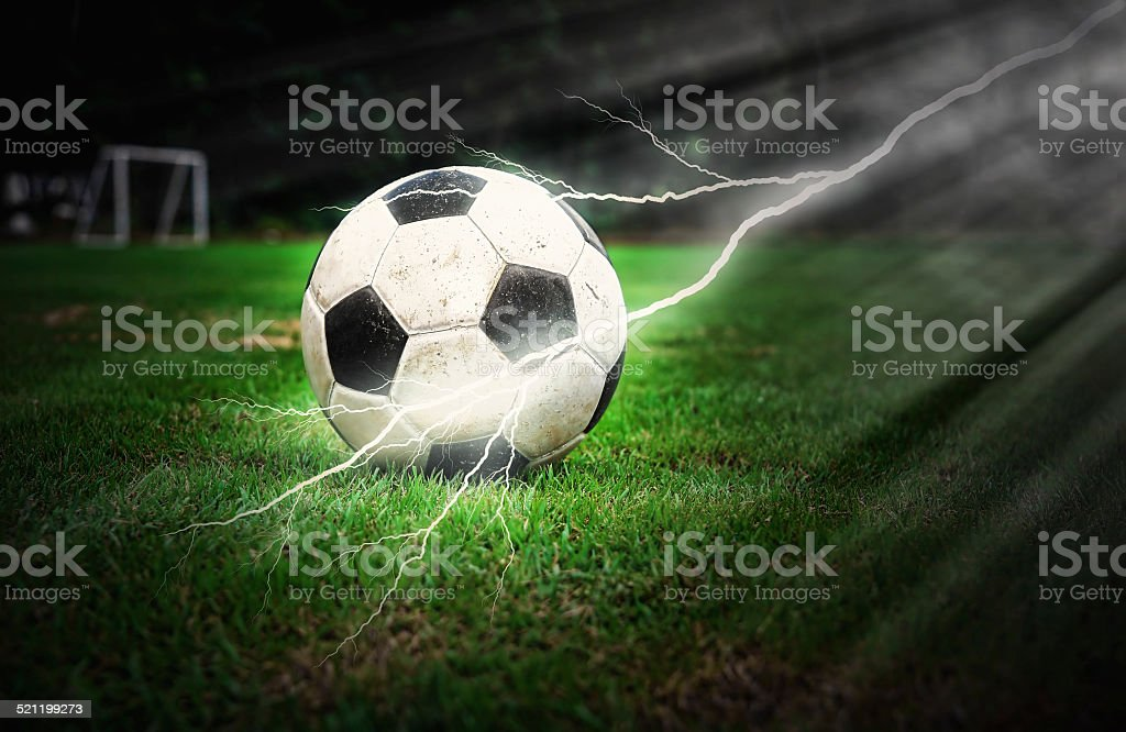 Football on green grass with lightning stock photo