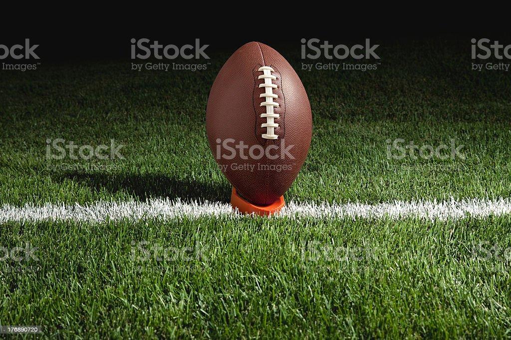 Football on tee at night stock photo