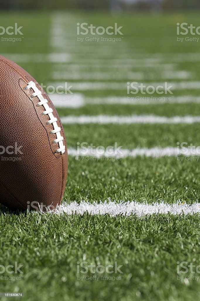 Football on white yard lines of football turf stock photo