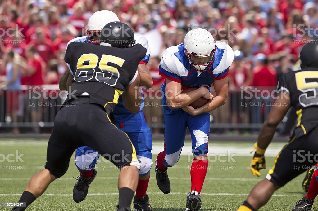 Football Player Carrying the Ball With Fans in Background. stock photo