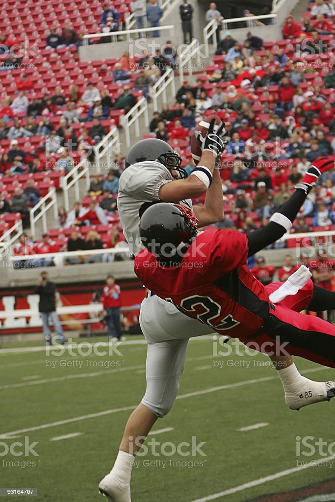 Football Player Catches Ball Under Heavy Pressure in Stadium Setting stock photo