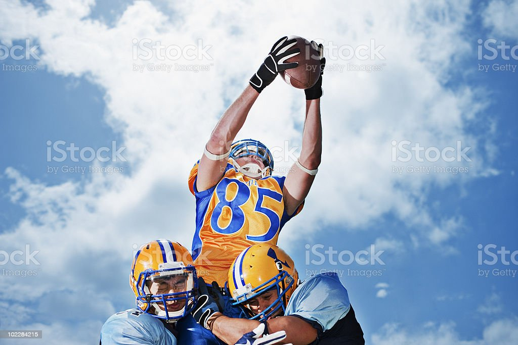 Football player catching football royalty-free stock photo