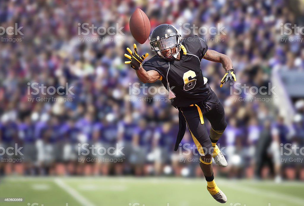 Football Player Diving to Catch a Football in Stadium. stock photo