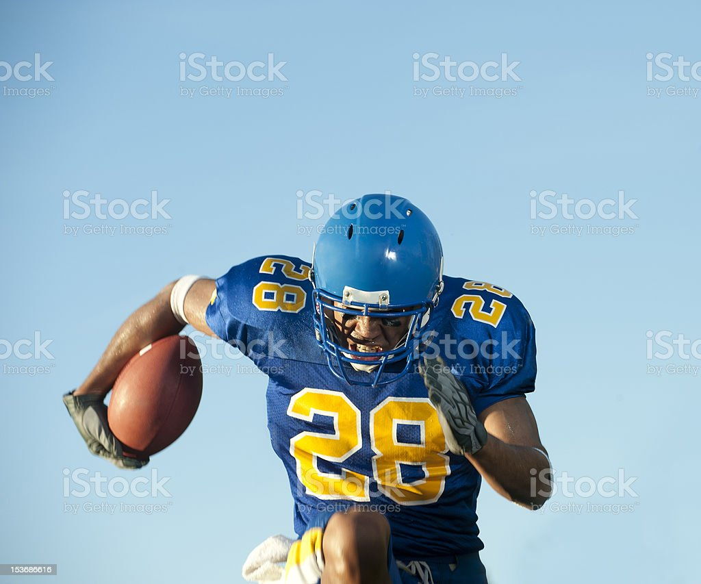 Football player holding a football while running stock photo