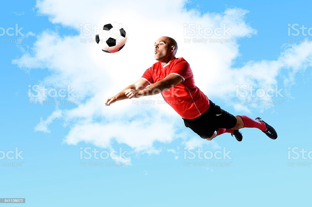 football player in action jumping for head kick isolated sky stock photo