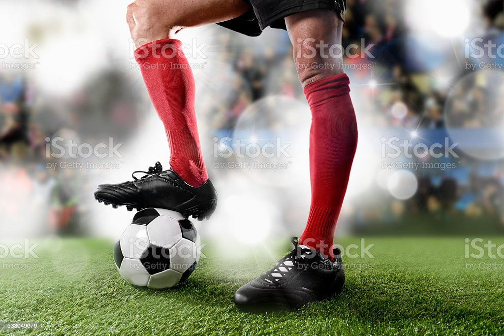 football player in red socks playing with ball on stadium stock photo