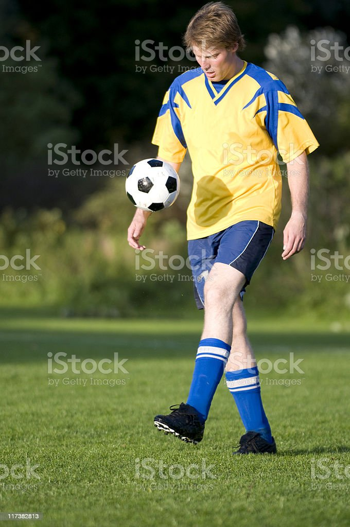 Football player juggles with a soccer ball royalty-free stock photo