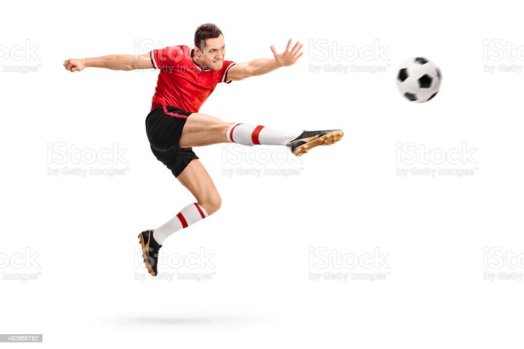 Football player kicking a ball in mid-air stock photo