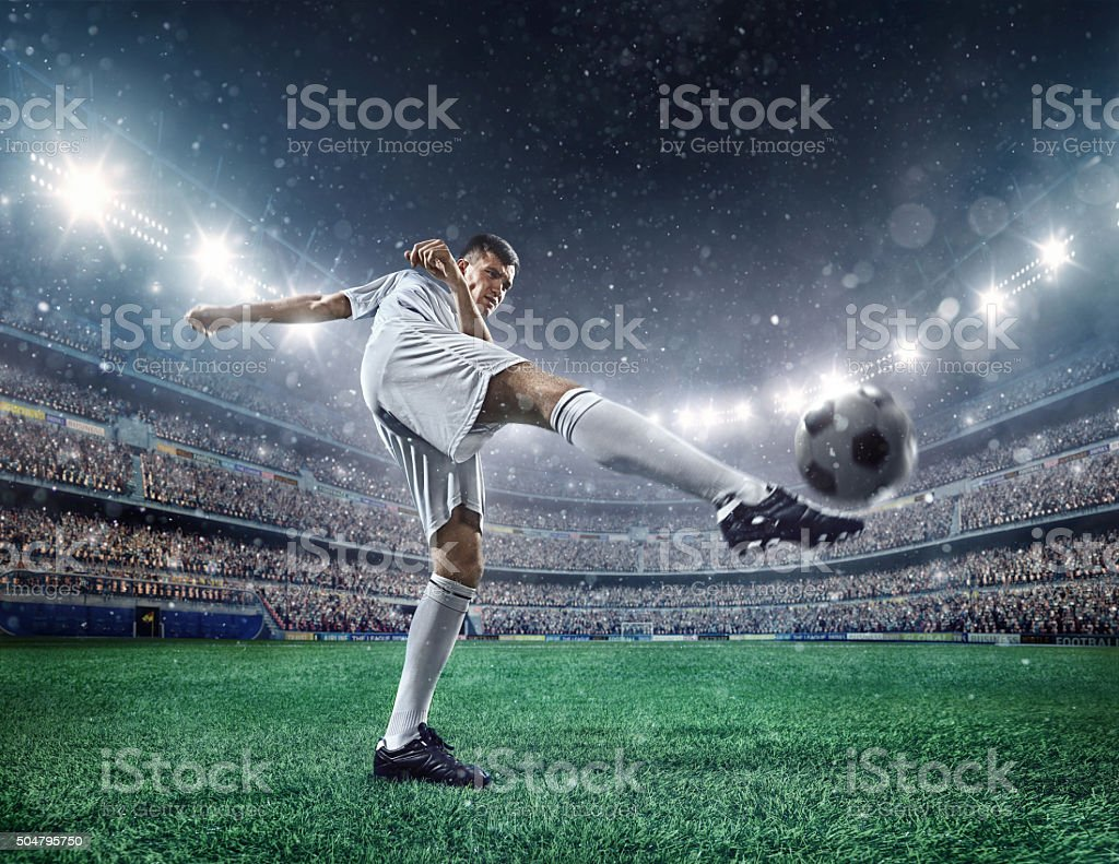 Football player kicking a ball stock photo