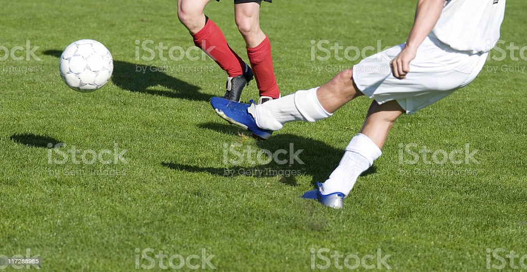 Football player kicks a soccer ball hard stock photo