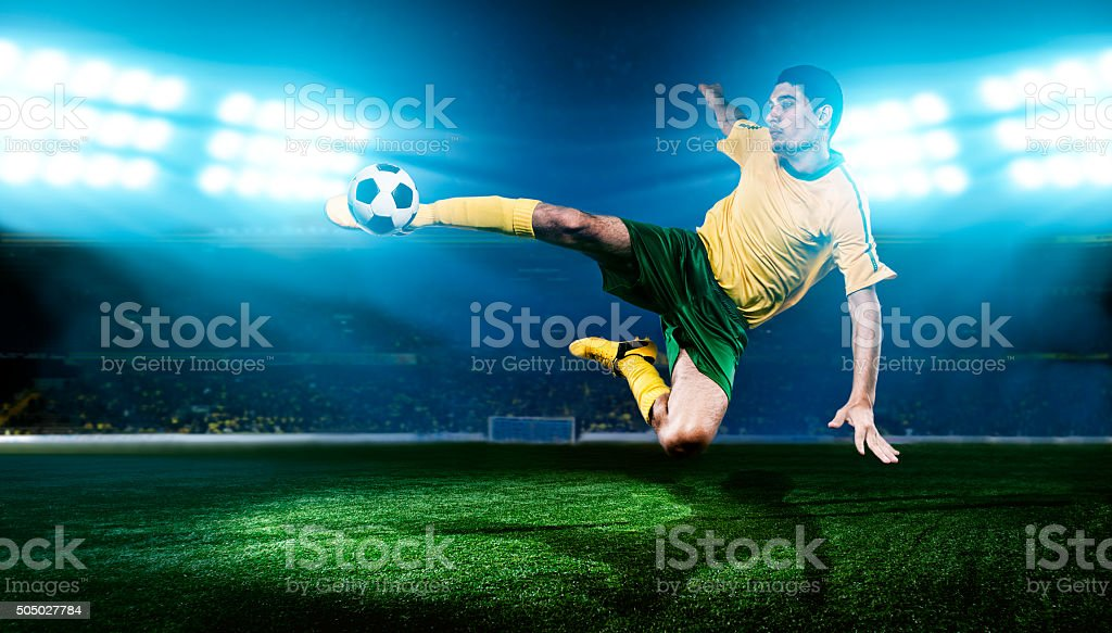 Football player kicks soccer ball in the air stock photo