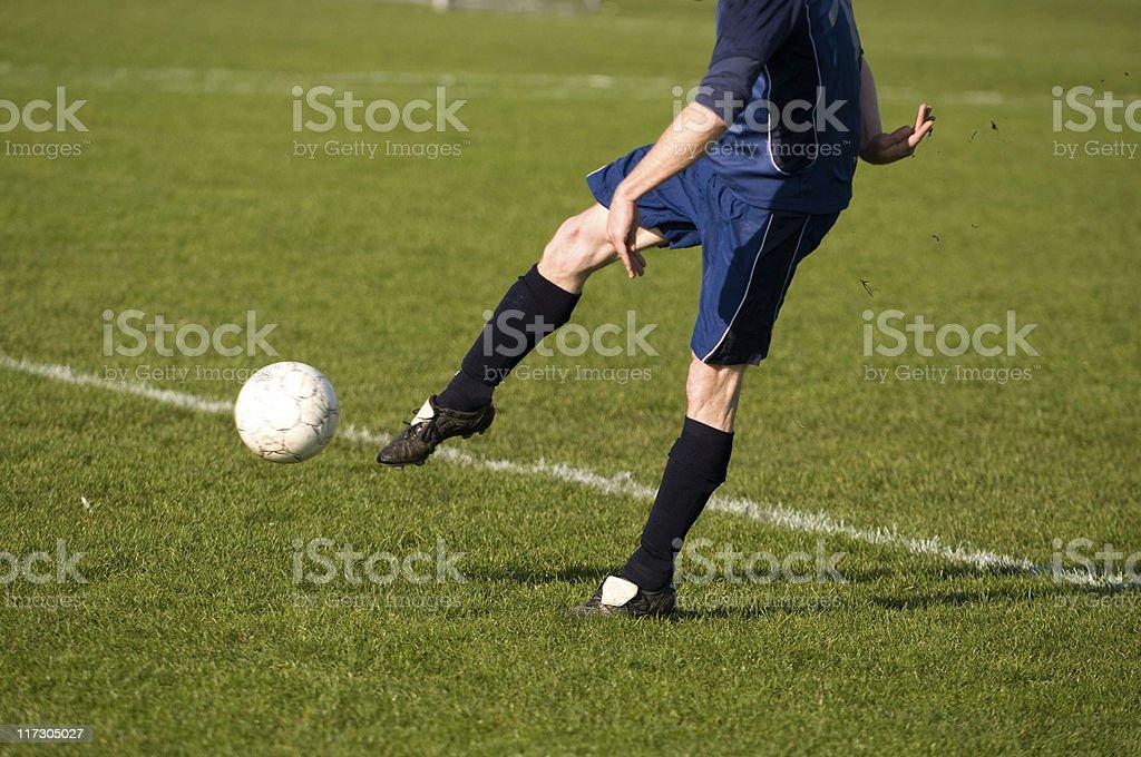 Football player kicks the ball towards goal stock photo