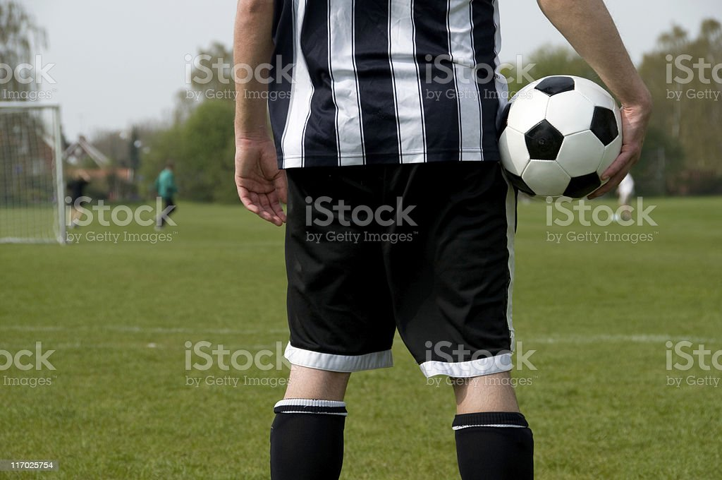Football player looks at match from the sideline royalty-free stock photo
