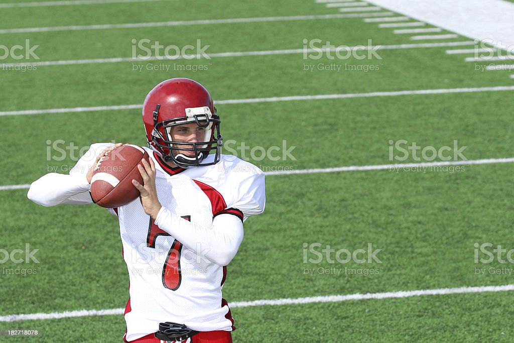 Football player on the field about to make a pass stock photo