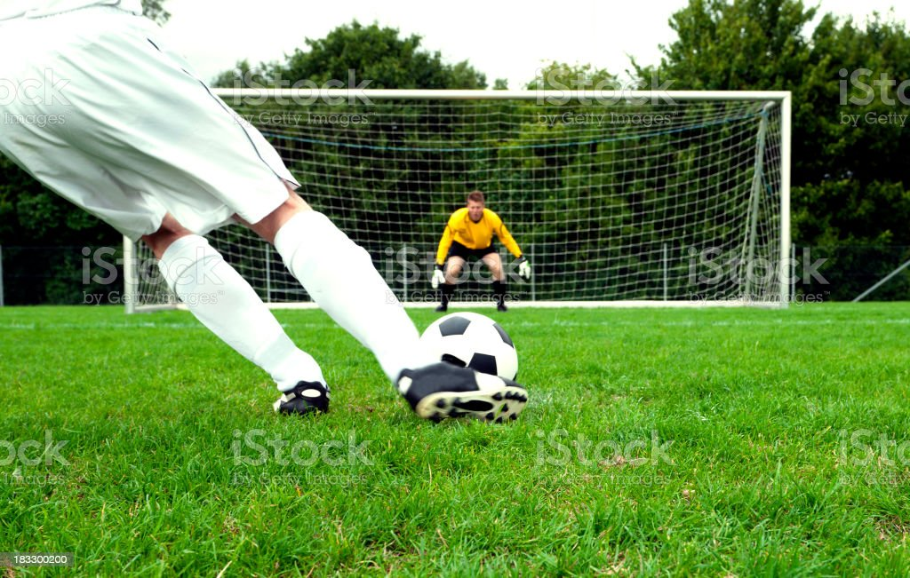 Football player performs a penalty kick on soccer pitch stock photo