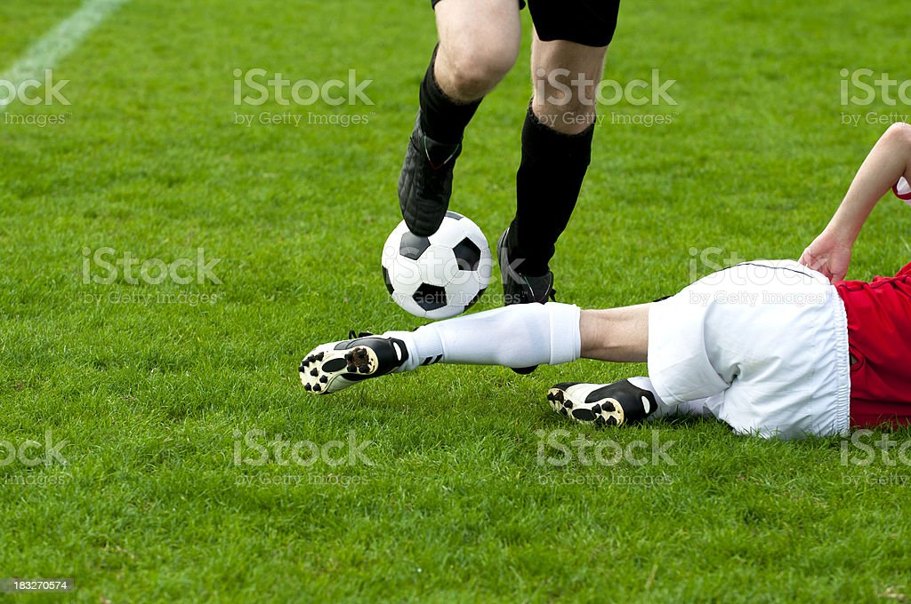 Football player performs a slide tackle to get the ball stock photo