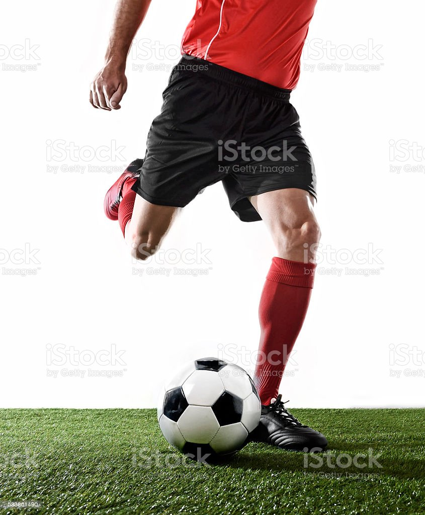 football player playing on grass pitch and kicking the ball stock photo