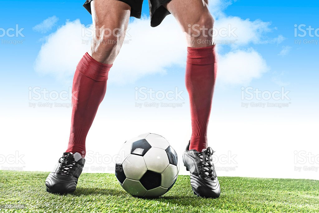 football player running and dribbling with ball playing outdoors stock photo
