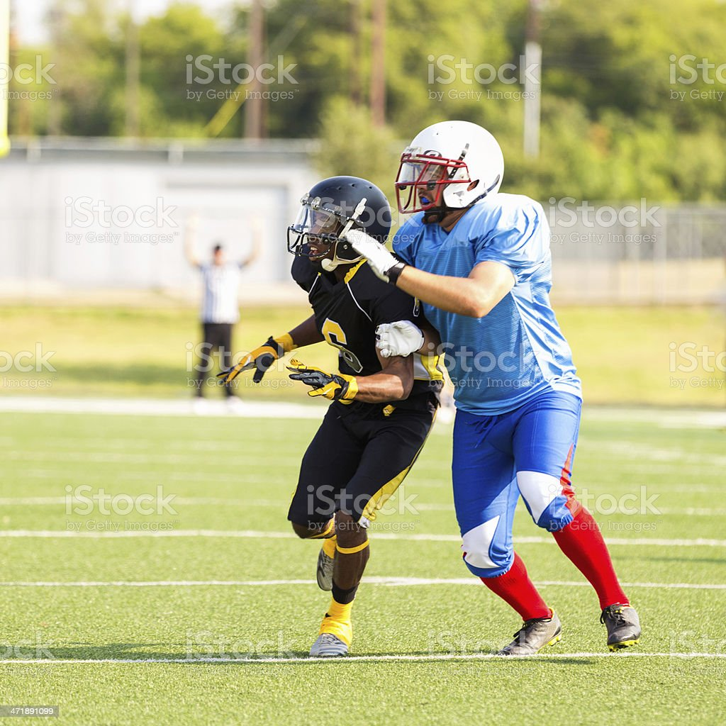 Football player running for interception during American game stock photo