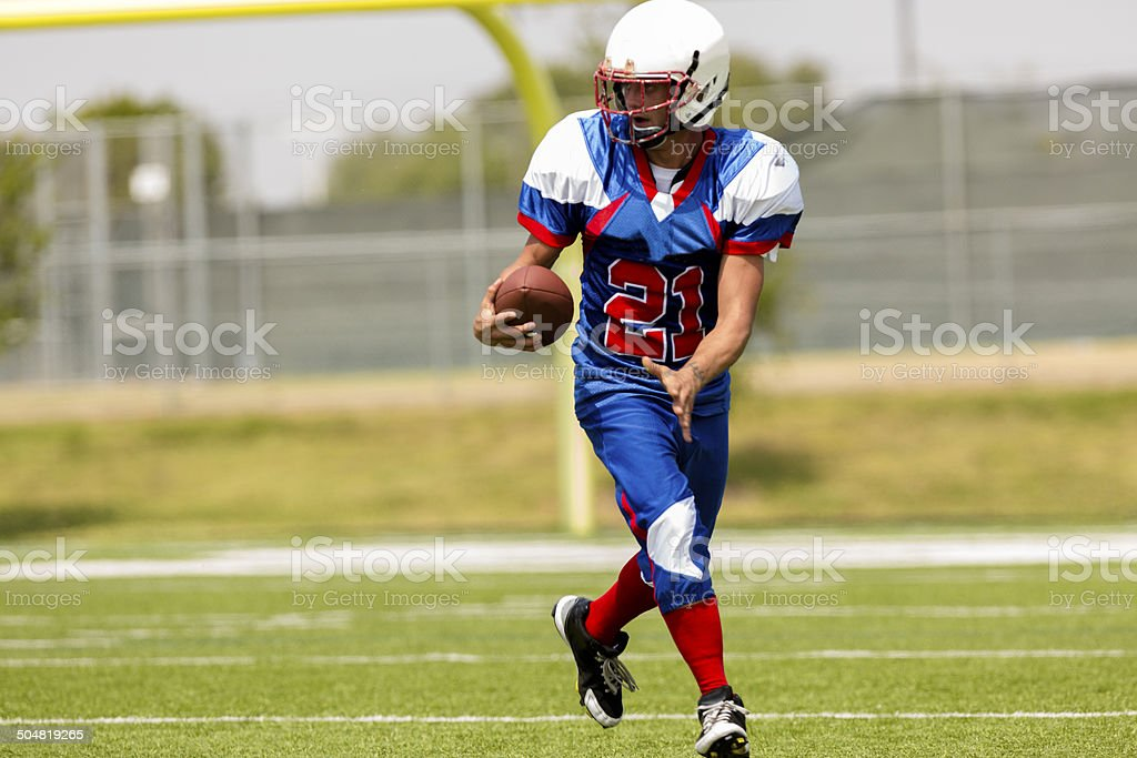 Football player running with ball on playing field. Goal post. stock photo
