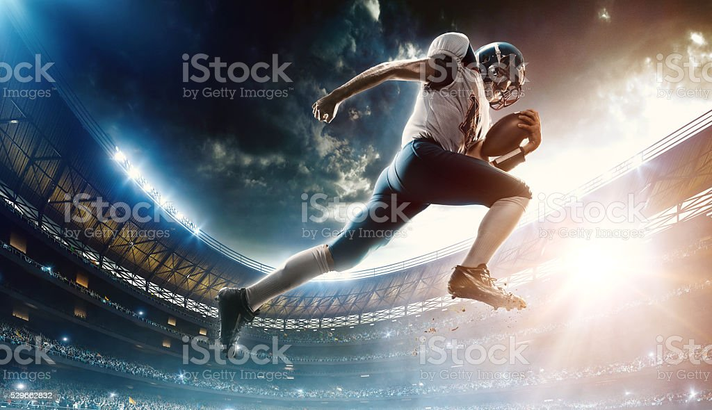 Football player runs with the ball stock photo