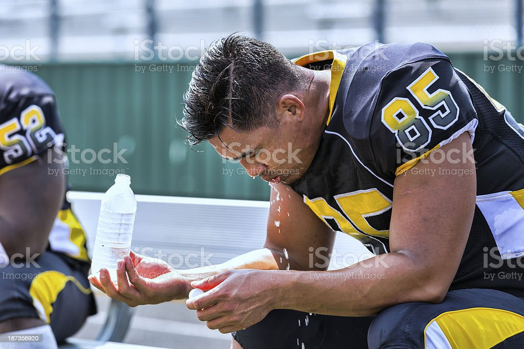 Football Player Sits on the Bench stock photo
