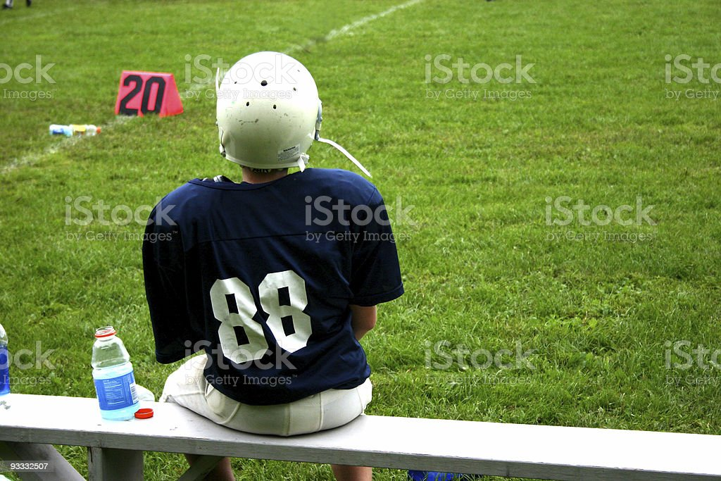 Football player sitting on a bench next to the field stock photo