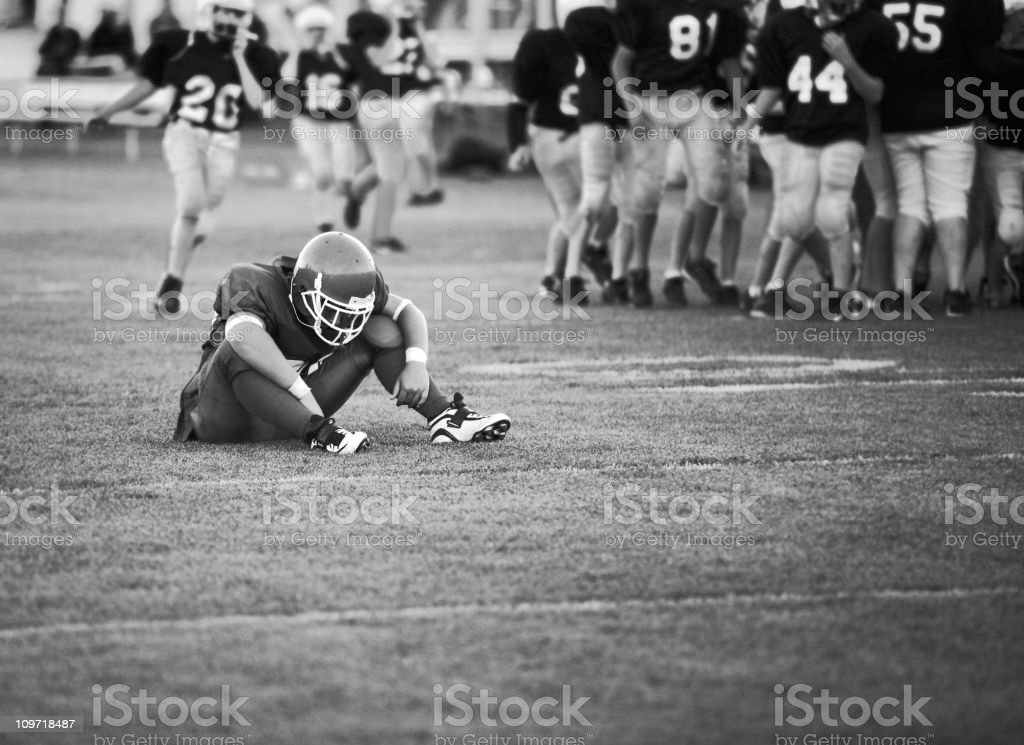 Football Player Sitting on Field stock photo