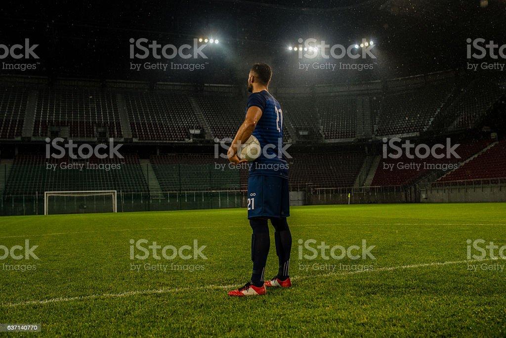 Football player standing in stadium stock photo