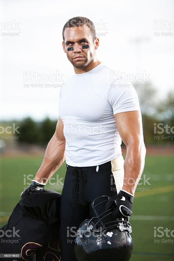 Football Player Standing with Pads and Helmet Off stock photo