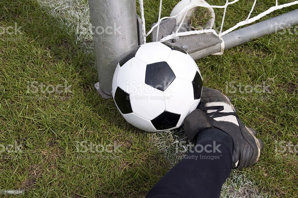 Football player stops the soccer ball before entering the goal royalty-free stock photo