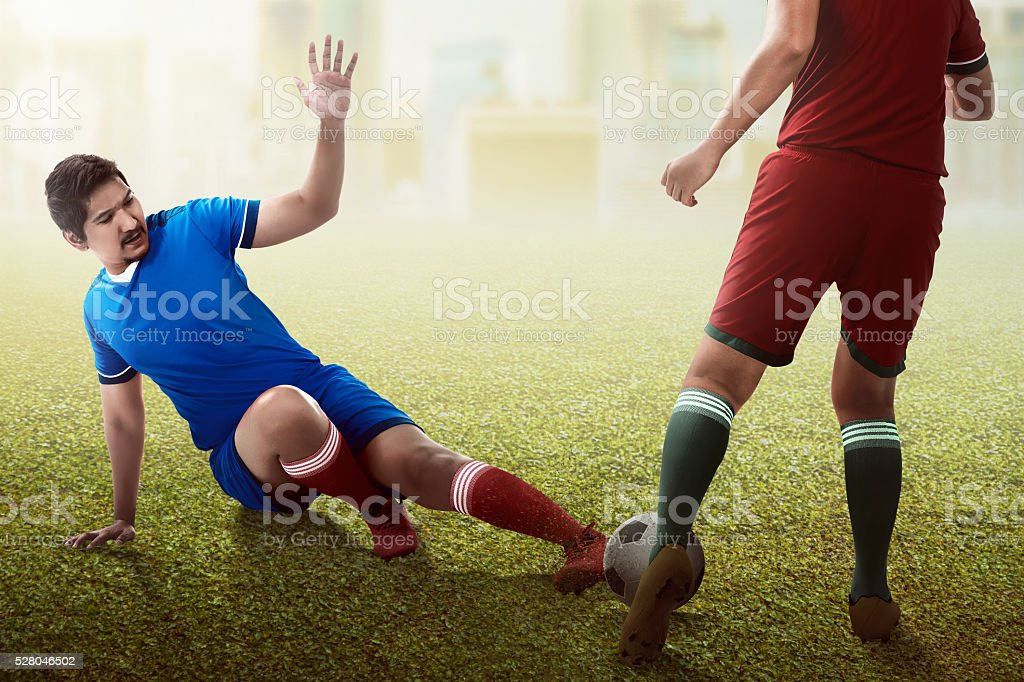Football player tackling for the ball stock photo