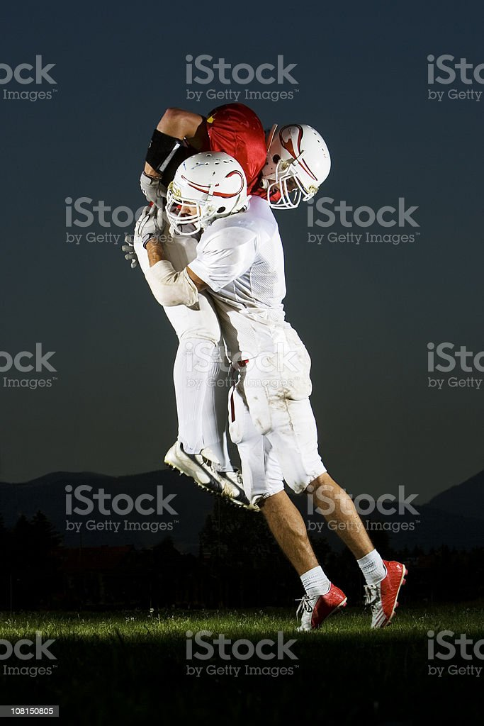 Football Player Tackling Other Man on Field stock photo