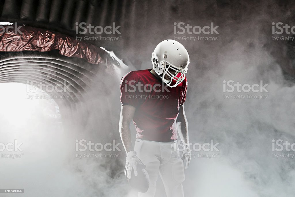 Football player walking out of a tunnel with fog around him royalty-free stock photo
