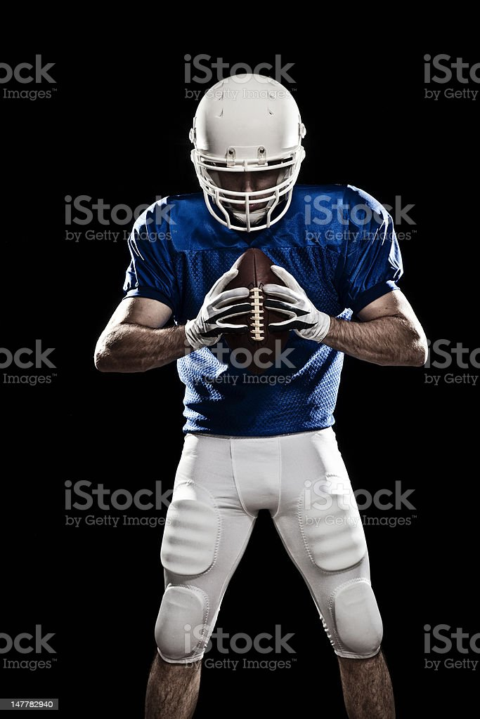 Football player with a ball in the hands, looking to the ball. Photo...