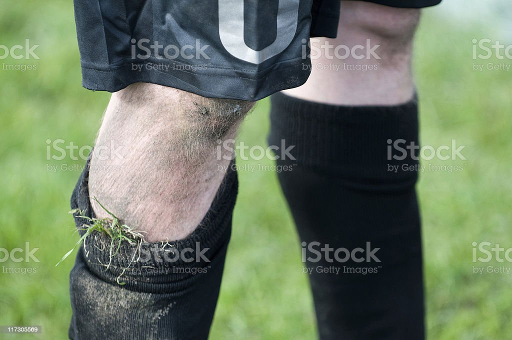 Football player with a dirty knee after a soccer match stock photo