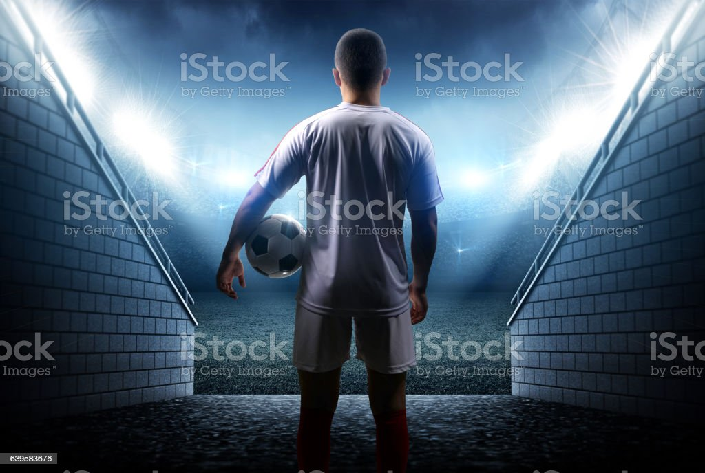 Football player with ball in the stadium stock photo