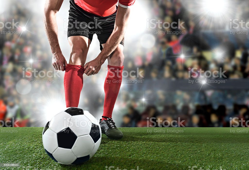 football player with ball wearing black shoes adjusting sock stock photo