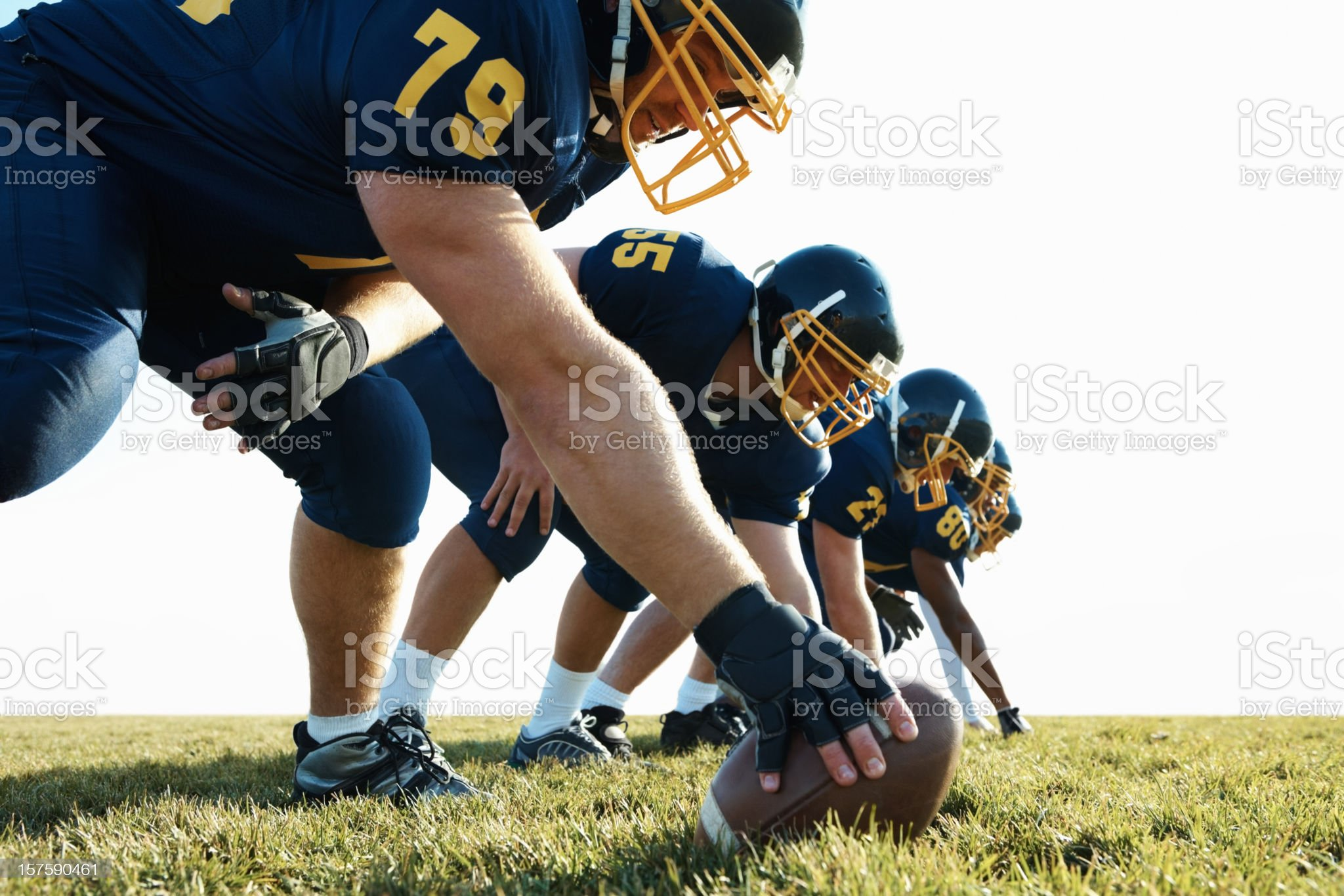 Football players bending at line of scrimmage royalty-free stock photo