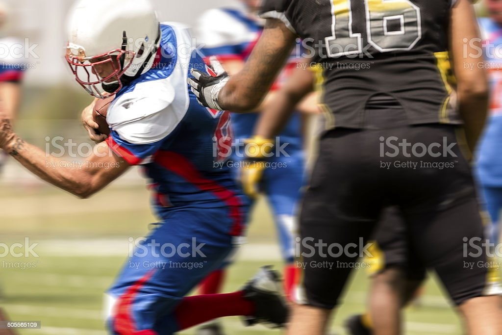 Football running back carries the ball. Defenders. stock photo